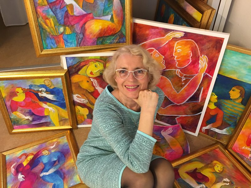 Alina Witwitzka sitting in front of her paintings in her studio, smiling
